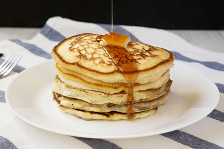 Homemade pancakes with butter and maple syrup on a white plate, side view. Closeup. Standard-Bild