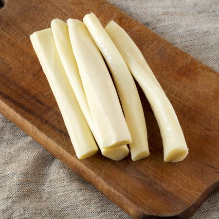 String cheese on a rustic wooden board, low angle view. Healthy snack. Close-up.