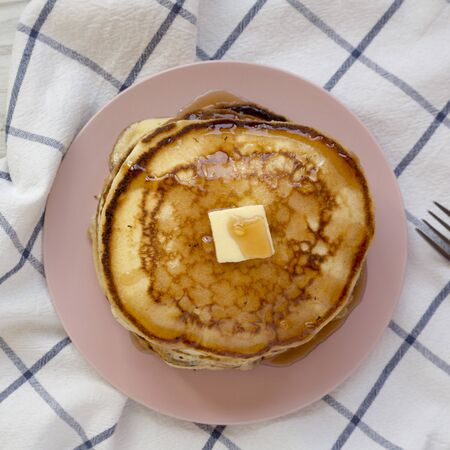 Homemade pancakes with butter and maple syrup on a pink plate, overhead view. Flat lay, from above, top view. Close-up.