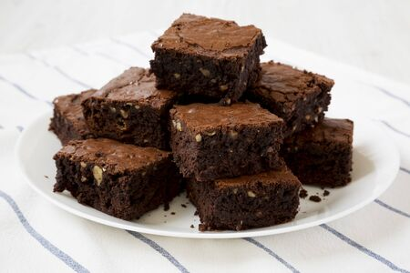 Homemade chocolate brownies on a white plate, side view. Close-up.