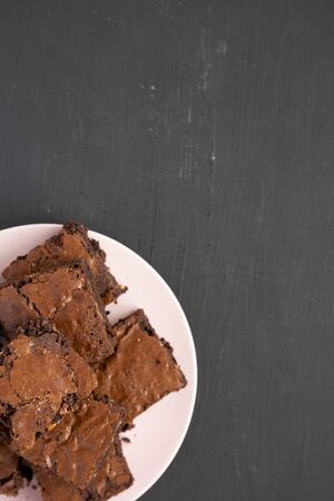 Homemade chocolate brownies on a pink plate on a black background, top view. From above, overhead, flat lay. Copy space.