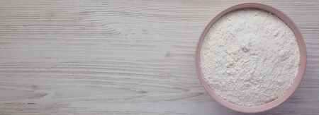 Gluten free rice flour in a pink bowl over white wooden surface,  top view. Flat lay, overhead, from above. Copy space. Stockfoto