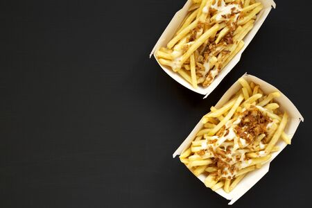 French fries with cheese sauce and onion in paper box on a black surface. Flat lay, overhead, top view. Copy space.