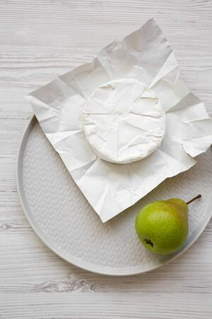 Camembert cheese on paper, fresh pear on a plate. Food for wine. Overhead, flat lay, top view, from above.