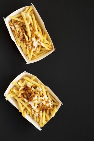 French fries with cheese sauce and onion in a paper box on a black background, top view. Flat lay, overhead, from above. Copy space.