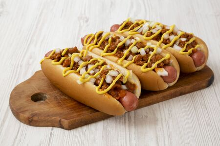 Homemade detroit style chili dog on a rustic wooden board on a white wooden background, side view. Close-up.
