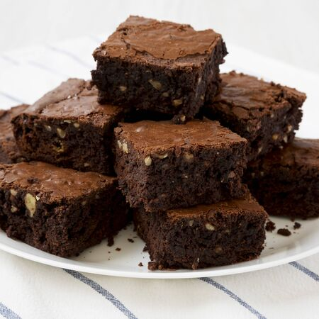 Homemade chocolate brownies on a white plate, side view. Closeup.