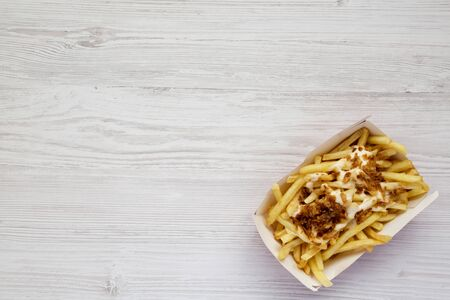 French fries with cheese sauce and fried onion in a paper box on a white wooden surface. Flat lay, from above, overhead. Copy space.