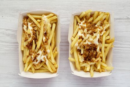 Top view, french fries with cheese sauce and fried onion in a paper box on a white wooden background. Flat lay, from above, overhead.