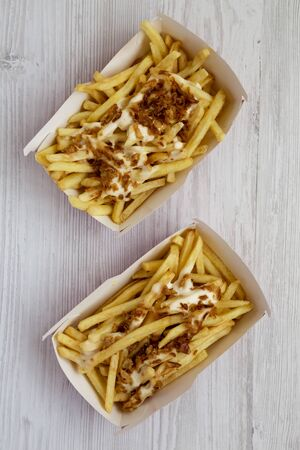French fries with cheese sauce and fried onion in paper boxes on a white wooden surface, top view. Flat lay, from above, overhead.