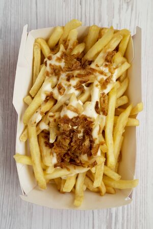 Fastfood: french fries with cheese sauce and fried onion in a paper box on a white wooden background, top view. Flat lay, from above, overhead. Close-up.