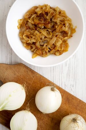 Homemade caramelized onions on a white plate on a white wooden surface, top view. Flat lay, overhead, from above. Close-up.
