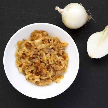Homemade caramelized onions on a white plate on a black background, overhead view. From above, top view, flat lay. Stock Photo