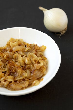 Homemade caramelized onions on a white plate on a black background, low angle view. Close-up. Stock Photo