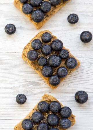 Vegan toasts with peanut butter, blueberries and chia seeds on a white wooden surface, overhead view. Healthy eating. Flat lay, from above.