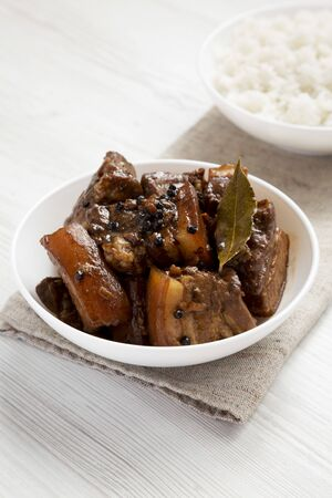 Homemade Filipino Adobo Pork with rice on a white wooden background, low angle view. Close-up.
