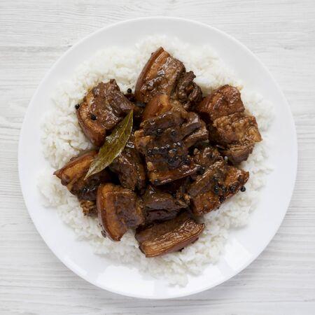 Porc Adobo philippin fait maison avec du riz sur une plaque blanche sur fond de bois blanc, vue de dessus. Mise à plat, au-dessus, d'en haut. Fermer. Banque d'images