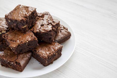 Homemade chocolate brownies on a white plate on a white wooden background, side view. Copy space.