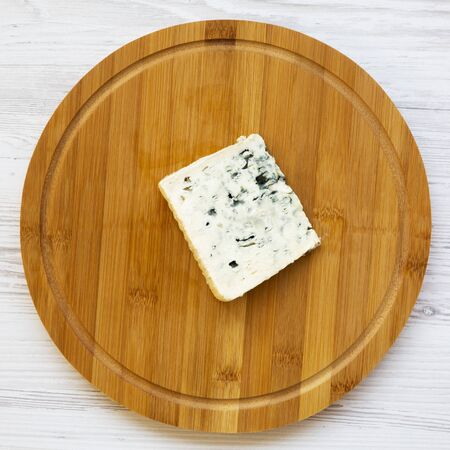 Blue cheese on a round bamboo board. Top view. Flat lay, overhead, from above.