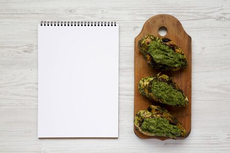 Grilled chimichurri chicken breast on a rustic wooden board, blank notepad on a white wooden background, top view. Copy space. 写真素材