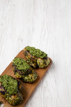 Grilled chimichurri chicken breast on a rustic wooden board on a white wooden surface, low angle view. Copy space.
