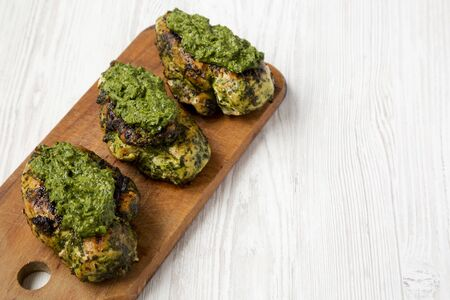 Grilled chimichurri chicken breast on a rustic wooden board on a white wooden background, low angle view. Space for text.