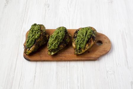 Grilled chimichurri chicken breast on a rustic wooden board on a white wooden surface, low angle view. 写真素材