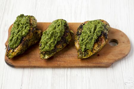 Grilled chimichurri chicken breast on a rustic wooden board on a white wooden background, low angle view. Close-up.