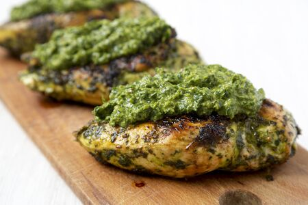 Grilled chimichurri chicken breast on a rustic wooden board on a white wooden background, side view. Close-up.