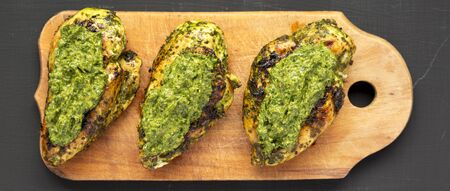 Grilled chimichurri chicken breast on a rustic wooden board on a black surface, top view. Flat lay, overhead, from above. 写真素材