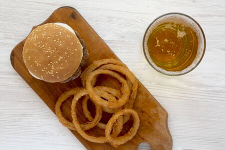 Homemade Mississippi Slug Burgers with onion rings and glass of cold beer on a white wooden background, overhead view. Flat lay, from above, top view. Standard-Bild