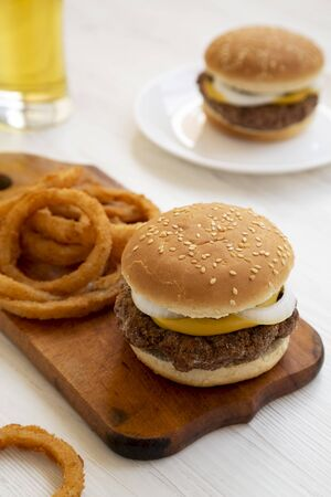 Homemade Mississippi Slug Burgers with onion rings and glass of cold beer on a white wooden surface, side view. Close-up.