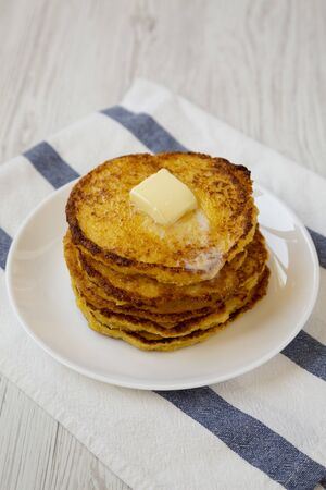 Homemade corn meal Johnny cakes with butter on a white plate, low angle view. Close-up. Standard-Bild