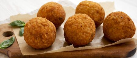 Homemade fried Arancini with basil on a rustic wooden board, side view. Italian rice balls. Close-up. Stockfoto