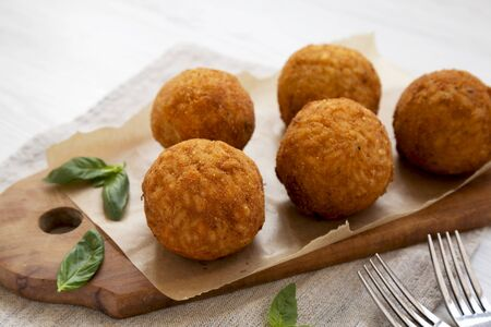 Homemade fried Arancini with basil on a rustic wooden board, side view. Italian rice balls. Close-up. 免版税图像