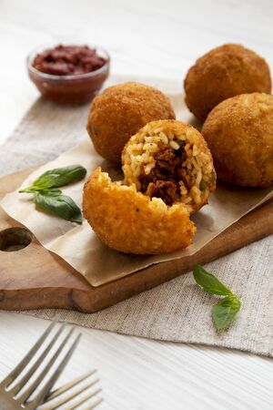 Homemade fried Arancini with basil and Marinara on a white wooden background, side view. Italian rice balls. Close-up.