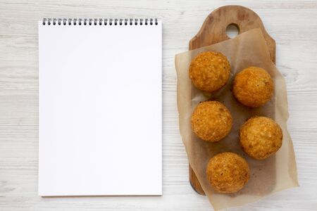 Homemade fried Arancini on a rustic wooden board, blank notepad on a white wooden background, top view. Flat lay, from above, overhead. Copy space.