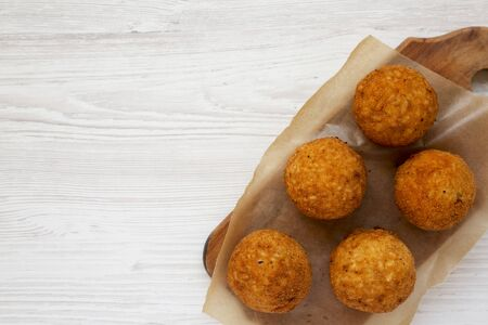 Homemade fried Arancini on a rustic wooden board on a white wooden surface, top view. Italian rice balls. Flat lay, from above, overhead. Space for text. Stock fotó