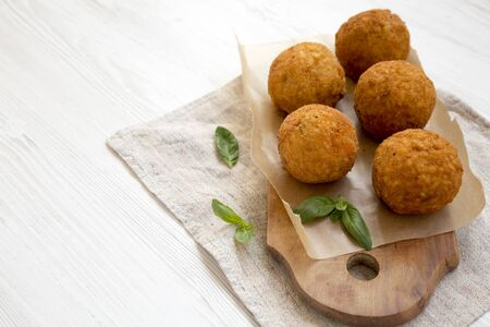 Homemade fried Arancini with basil on a rustic wooden board, side view. Italian rice balls. Copy space. Stock fotó