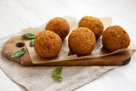 Homemade fried Arancini with basil on a white wooden surface, side view. Italian rice balls. Close-up. Stock fotó