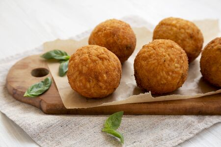Homemade fried Arancini with basil on a white wooden background, side view. Italian rice balls. Close-up.