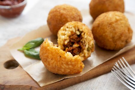 Homemade fried Arancini with basil and Marinara on a white wooden table, side view. Italian rice balls. Close-up. Stock fotó