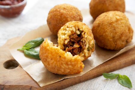Homemade fried Arancini with basil and Marinara on a white wooden background, side view. Italian rice balls. Closeup. Stock fotó
