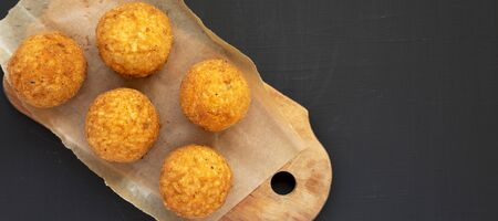 Homemade fried Arancini on a rustic wooden board on a black surface, overhead view. Italian rice balls. Flat lay, from above, top view. Copy space. Stock fotó