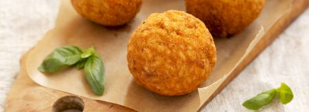 Homemade fried Arancini with basil on a rustic wooden board, low angle view. Italian rice balls. Close-up. Stock fotó