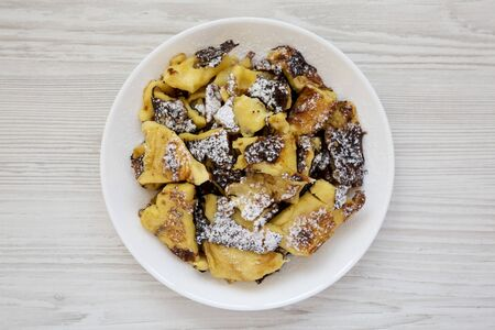 Homemade german Kaiserschmarrn pancake on a white plate over white wooden background, top view. Flat lay, overhead, from above. 版權商用圖片