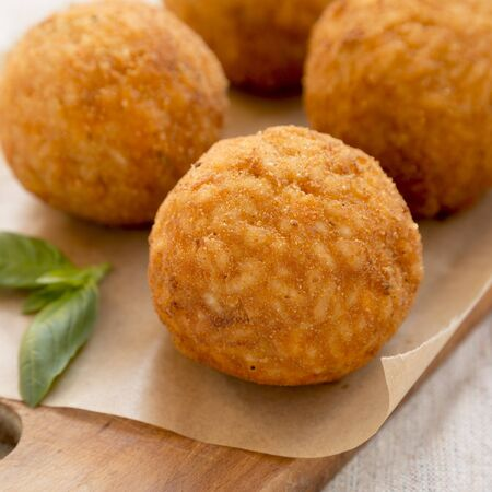Homemade fried Arancini with basil on a rustic wooden board, side view. Italian rice balls. Close-up. Stock fotó