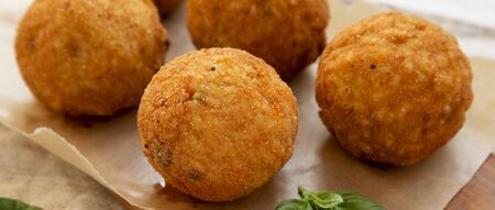 Homemade fried Arancini with basil on a rustic wooden board, low angle view. Italian rice balls. Closeup.