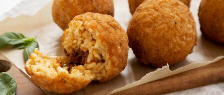Homemade fried Arancini with basil on a rustic wooden board, side view. Italian rice balls. Closeup. Stock fotó