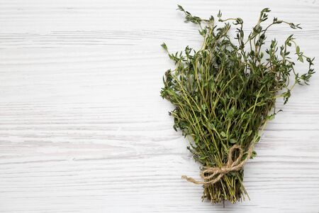 Raw organic fresh thyme on a white wooden background, top view. Flat lay, overhead, from above. Copy space.